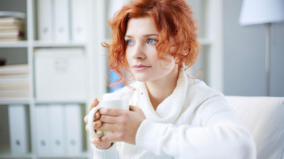 Woman thinking while holding tea cup